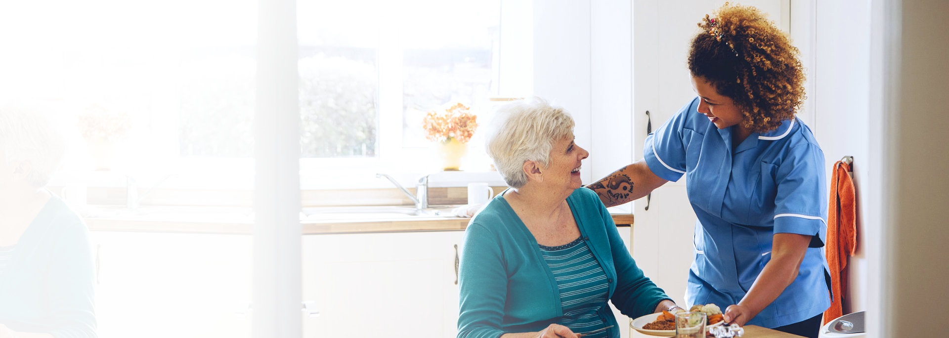 senior woman having a meal with her caregiver