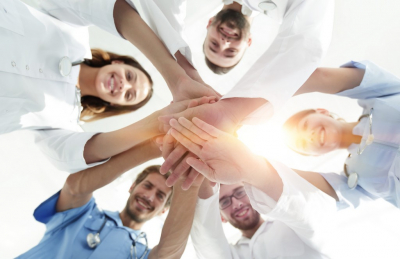 group of medical professionals joining hands